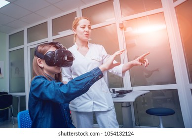 Ophthalmology doctor checks the girl's vision with the help of virtual reality goggles. Virtual training. Optometry