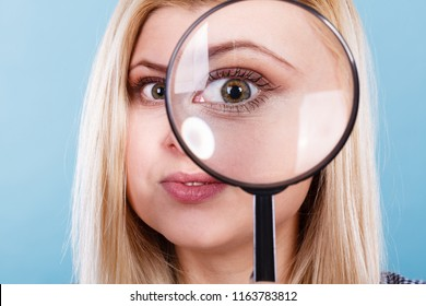 Ophthalmology, spy accessories, eyesight concept. Woman looking through magnifying glass having big one eye.