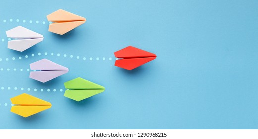 Opinion leadership concept. Red paper plane leading another colorful ones, influencing the crowd, blue background, panorama