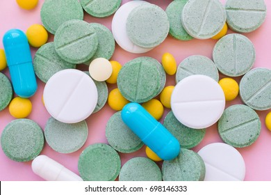 Opioid Pills. Opioid epidemic and drug abuse concept. Different tablets, pills, capsule on a pink background.  Heap mix therapy drugs.