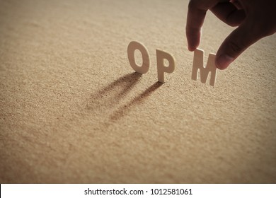 OPM wood word on compressed or corkboard with human's finger at M letter.