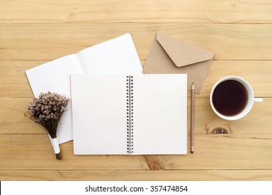 Opned blank notebook with cup of tea on the wood desk, top view