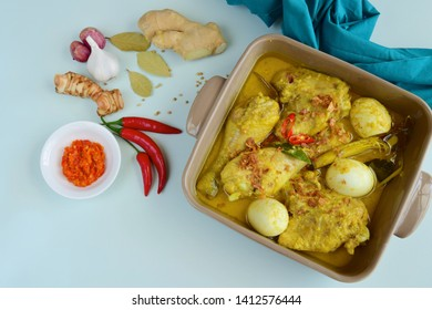 Opor ayam, chicken cooked in coconut milk added with boiled eggs. Originated from Central Java, Indonesia, served with sambal. Popular dish for lebaran or Eid al-Fitr . Flat lay