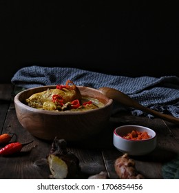 Opor ayam is an Indonesian dish consisting of chicken cooked in coconut milk, on textured table, with chili, and other seasoning around, on wooden table