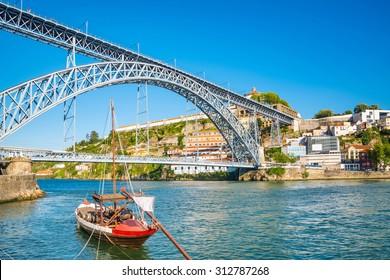 Oporto or Porto city skyline, Douro river, traditional boats and Dom Luis or Luiz iron bridge. Portugal, Europe.