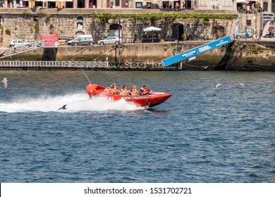 Oporto, Portugal - July 19, 2019: Xtreme Jet Boat River Safari in Porto, Portugal. High speed red boat over Douro river