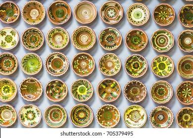 OPOSHNYA, UKRAINE - August 2017: Ukrainian pottery. Pottery market in Ukrainian village Oposhnya, center of Ukrainian pottery production. Small clay plates hanging on wall in pottery museum, Ukraine