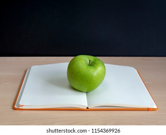 oppen notebook and a green apple in front of blackboard
