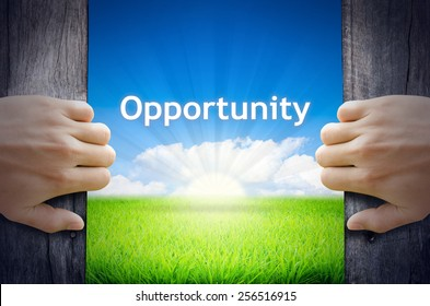 Opportunity. Hand opening an old wooden door and found Opportunity word floating over green field and bright blue Sky Sunrise.