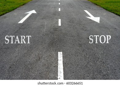 Opposite arrow on the asphalt road with text start and stop.