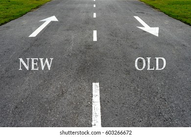 Opposite arrow on the asphalt road with text new and old.