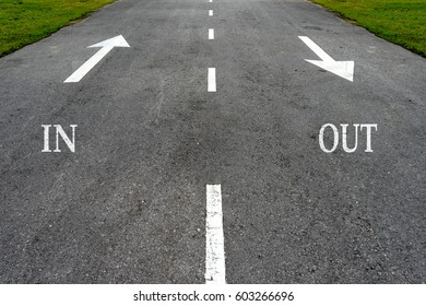 Opposite arrow on the asphalt road with text in and out.