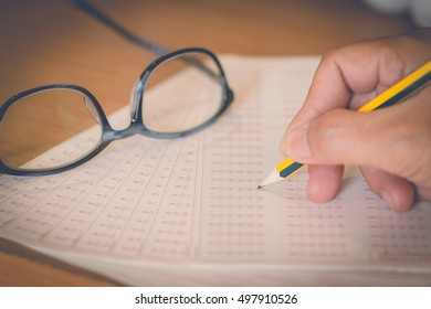 optical form of an examination with pencil and glasses, filling a standardized test form
