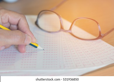 optical form of examination with pencil and glasses, filling standardized test form