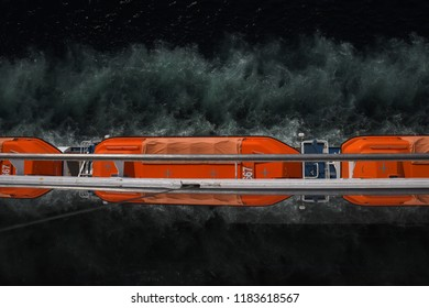 Optical illusion of orange life boats on a ship
