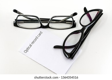 Optical record card with two pais of black glasses with lenses isolated against a plain white background