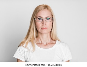 Optical Shop. Portrait of middle-aged woman in glasses looking at camera isolated over gray studio wall, copyspace