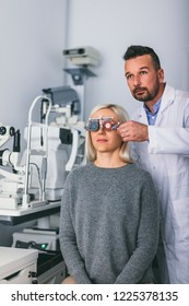Optician checking patient's eyesight with trial frame. Doctor's appointment and medical test.
