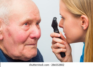 Optician consulting elderly patient with cataracts and other eye problems.
