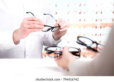 optician and customer choosing new glasses and trying different models eye doctor with client comparing
