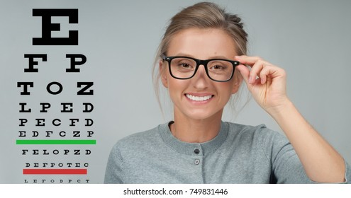 Optician. Eyesight check. Woman in glasses on the background of eye test chart, eye care concept