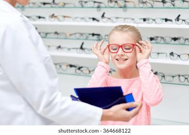 optician and girl choosing glasses at optics store