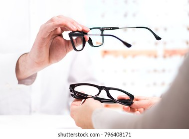 Optician giving new glasses to customer for testing and trying. Eye doctor showing patient lenses in spectacles store. Professional optometrist in white coat with client.