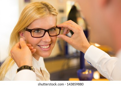 Optician or optometrist consulting a customer about eyeglasses, spectacles and frames in a shop