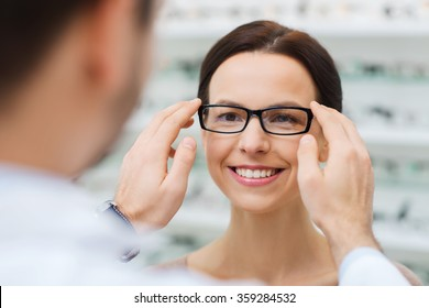 optician putting glasses to woman at optics store