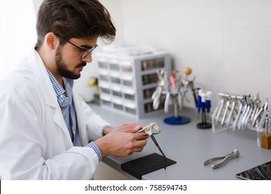 Optician repairing and fixing eye glasses