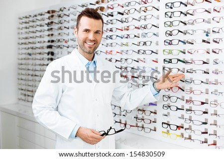 Optician selling glasses. Eye doctor, optometris at work.