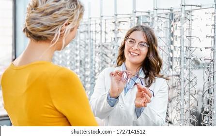Optiker, der eine Brille in einem optischen Geschäft vorschlägt und zeigt, den richtigen Rahmen für verschreibungspflichtige Brillen findet