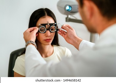 Optician with trial frame and patient at clinic