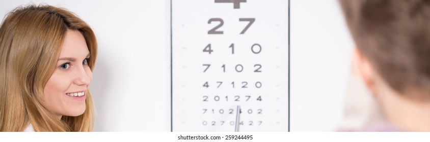 Optician using Snellen test during eye examination