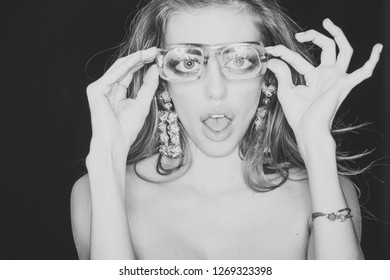 Optics store concept. Beauty girl with makeup and big earrings jewelry, dark background. Woman with surprised face wears ugly eyeglasses for vision. Girl short sightedness needs modern eyeglasses.