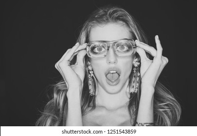 Optics store concept. Girl short sightedness needs modern eyeglasses. Beauty girl with makeup and big earrings jewelry, dark background. Woman with surprised face wears ugly eyeglasses for vision