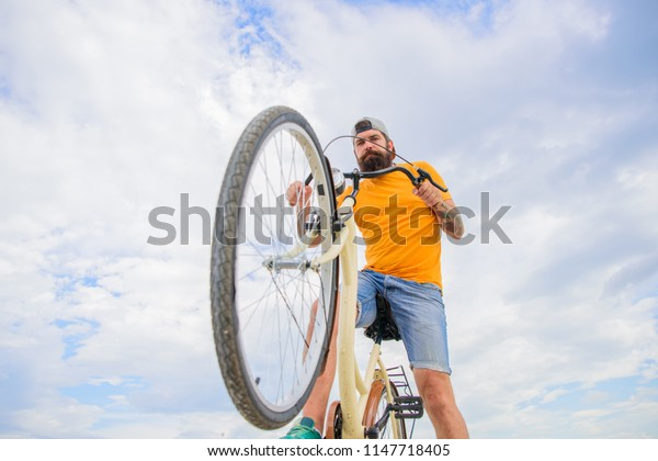 Optimise cycling performance. Man bearded hipster rides bicycle bottom view sky background. Modern bicycle riding culture. Overcome obstacles on bike. Hipster ready to perform trick.