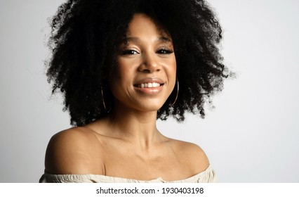 Optimist Young female model of afro appearance. Photo shoot in a photo studio on a white background. Beautiful clean smooth skin of the face. Black healthy curly hair.