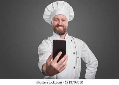 Optimistic adult bearded professional cook in white chef uniform taking selfie on mobile phone against gray background