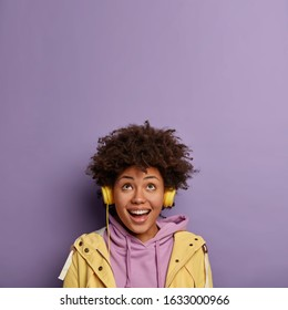 Optimistic African American woman got new headphones from friend, enjoys listening music from playlist and positive vibes, wears hoodie and yellow anorak, looks above against purple background.