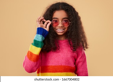 Optimistic African kid in colorful sweater smiling for camera and adjusting sunglasses against beige background