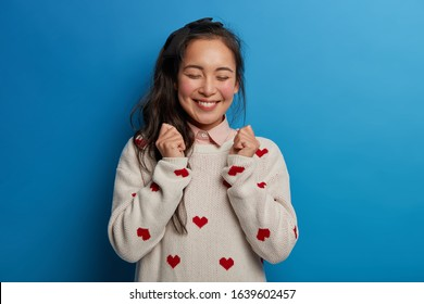 Optimistic Asian girl raises clenched fists, anticipates for good results of exam, closes eyes and smiles broadly, has pony tail, wears sweater isolated on blue background. People, emotions, lifestyle