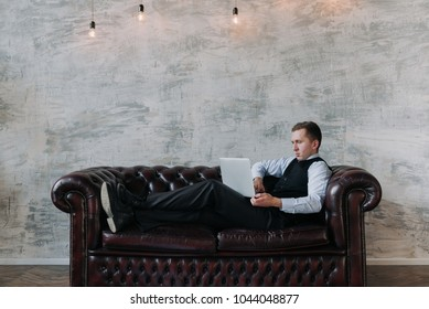 Optimistic attractive businessman relaxing after a working day