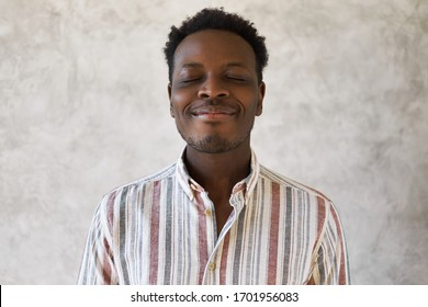 Optimistic attractive young dark skinned malewith Afro hairstyle posing with eyes closed and joyful smile, having peaceful facial expression, practicing meditation. Black guy smiling in his sleep