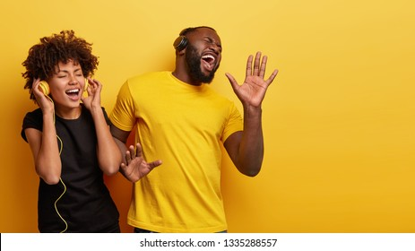 Optimistic black female and male enjoys favourite moment in song, smile from joy and pleasure, dance while listen music in headphones, sing aloud, isolated over yellow wall with free space right