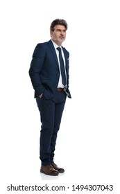 Optimistic businessman holding both hands in his pockets and hopefully looking away while wearing a blue suit and standing on white studio background