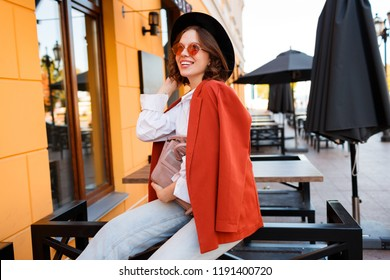 Optimistic carefree girl in cute orange sunglasses, jacket and black hat sitting outdoor.  utumn fashion. Street cafe  background with yellow walls.