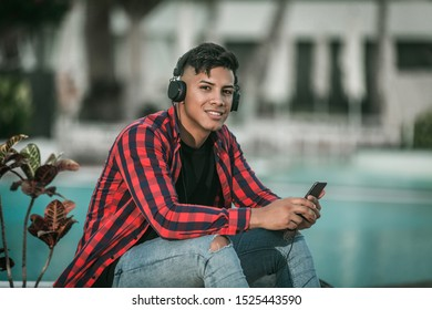 Optimistic ethnic man in casual outfit and headphones smiling and looking at camera while sitting on blurred background of pool outside hotel