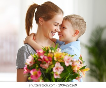Optimistic family: mother with bouquet of  alstroemeria laughing and touching nose with happy son  during holiday celebration  mothers day at home - Shutterstock ID 1934226269