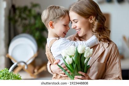 Optimistische Familie: Mutter mit Tulpenstrauch, die mit glücklichem Sohn während der Feiertagsfeiertage im Haus lächelt und die Stirn berührt